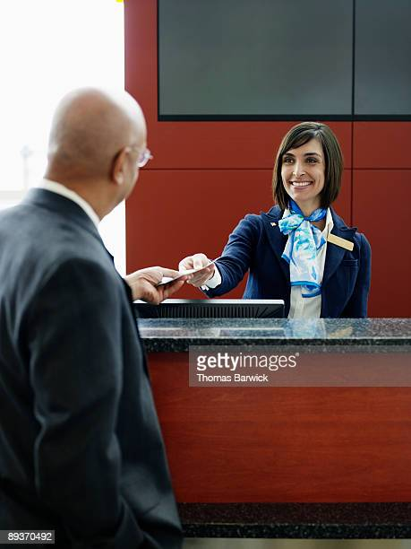 Ticket agent handing passenger boarding pass
