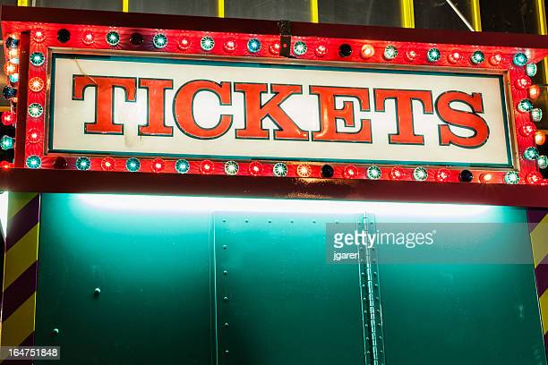 A ticket booth lights the midway at night at a fair