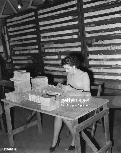 A ticket clerk checks through some of the unsold tickets to the 1948 Summer Olympics in London in her office at the Empire Pool in Wembley London...