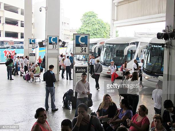 Ticket collector outside Brazilian coach with passengers queing