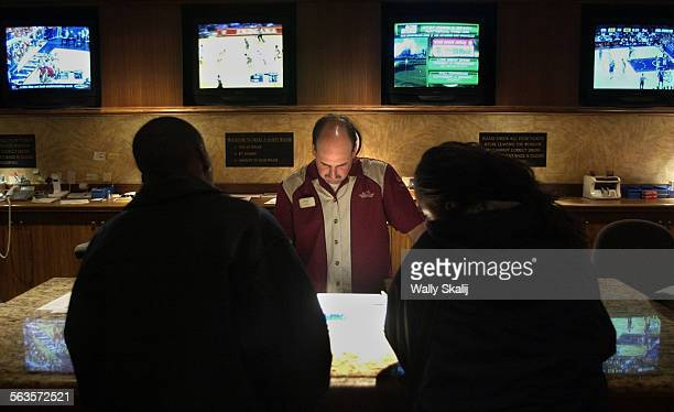 Ticket writer Dave Behrends takes a customers bet at the Mandalay Bay sports book in Las Vegas Billions of dollars will be wagered on Super Bowl...
