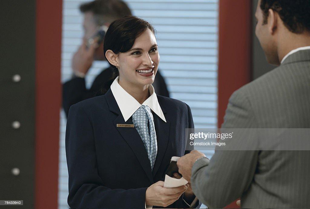 Ticketing agent taking boarding pass : Stockfoto