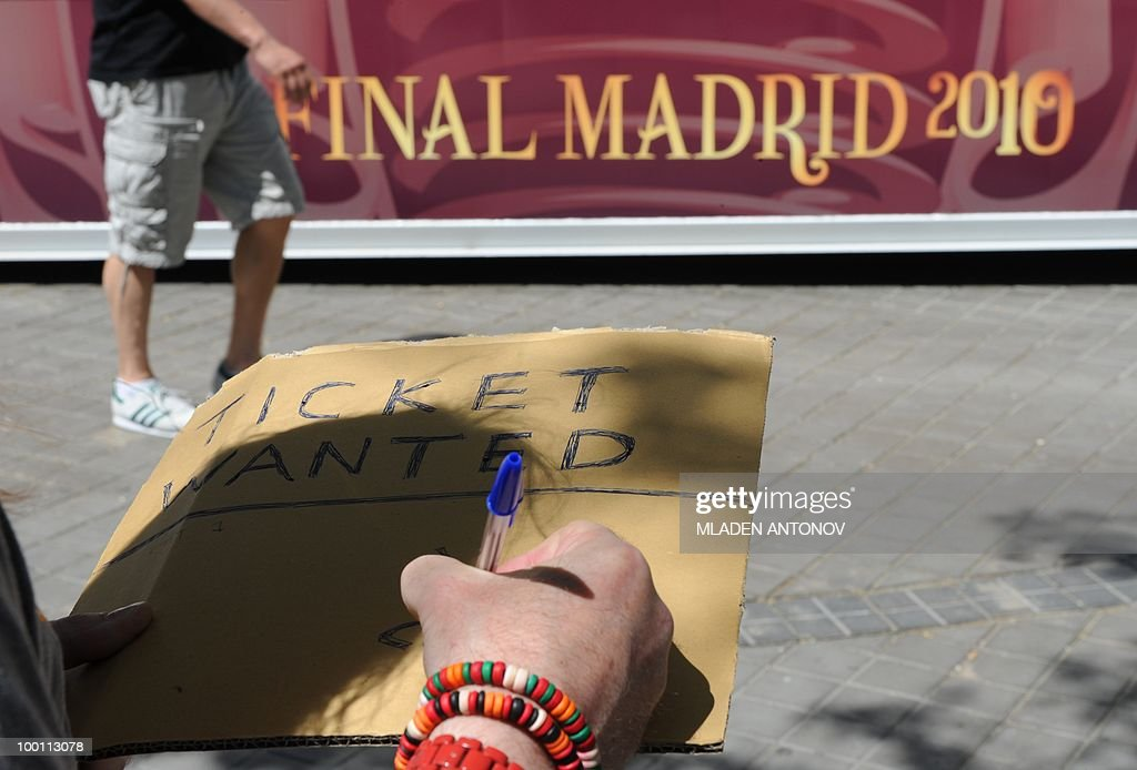 A ticketless British soccer fan writes a request for a ticket for the UEFA Champions League final football match outside the Santiago Bernabeu stadium in Madrid, on May 21, 2010. Inter Milan will face Bayern Munich in the UEFA Champions League final match to be played at the Santiago Bernabeu Stadium in Madrid on May 22, 2010.