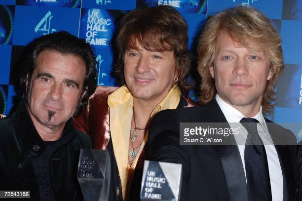 Tico Torres Richie Sambora and Jon Bon Jovi of rock group Bon Jovi pose with their inductee trophy in the Awards Room at the UK Music Hall Of Fame...