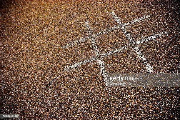 Tic-Tac-Toe Lines on Pebbled Pavement