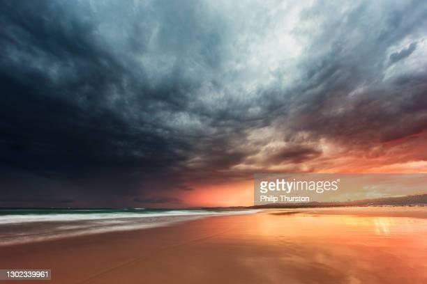 getijderetraite die dramatische onweer op het strand bij zonsondergang weerspiegelt - dramatische lucht stockfoto's en -beelden