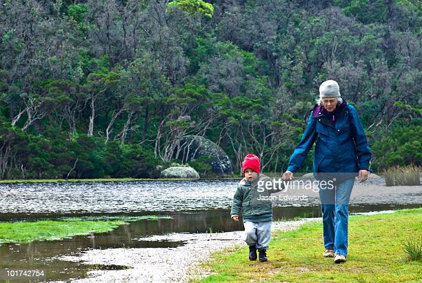 A toddler holding hands with his grandmother as they walk by a river.