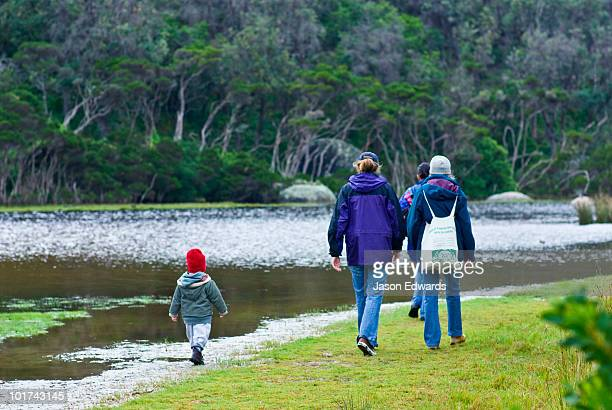 A small boy follows his mother and grandmother on a walk by a river.