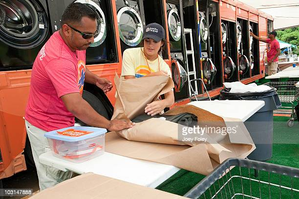 Tide crew members fold and pack clothes for residents that have dropped off their laundry at the Tide Loads Of Hope free mobile laundry services for...