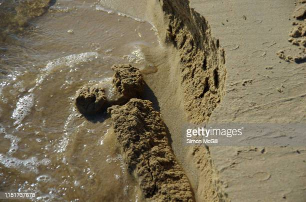 tide eroding sand from a beach - collapsing stock pictures, royalty-free photos & images