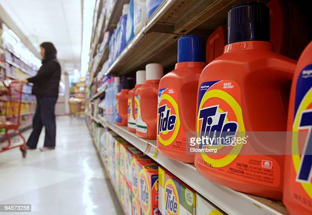 Tide laundry detergent products sit on a shelf as a shopper browses down the aisle in a supermarket in New York Tuesday Oct 30 2007 Procter Gamble Co...