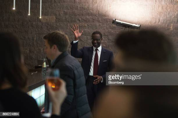 Tidjane Thiam chief executive officer of Prudential Plc waves to Maurice Levy chief executive officer of Publicis Groupe SA not pictured as he...