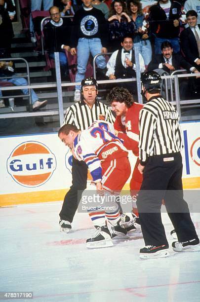 Tie Domi of the New York Rangers fights with Bob Probert of the Detroit Red Wings on December 2 1992 at the Madison Square Garden in New York New York