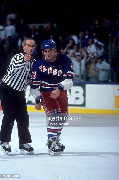 Tie Domi of the New York Rangers is escorted to the penalty box after a fight during an NHL preseason game against the New York Islanders in...
