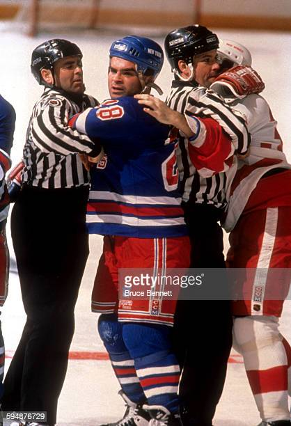 Tie Domi of the New York Rangers is held back by linesman Randy Mitton during an NHL game against the Detroit Red Wings on February 9 1992 at the...