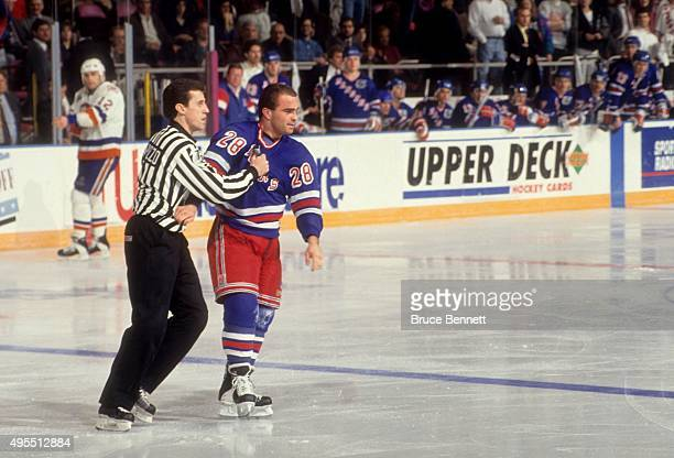 Tie Domi of the New York Rangers is held by the linesman after fighting during the game against the New York Islanders on February 14 1992 at the...