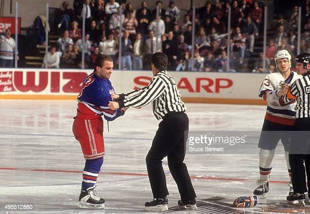 Tie Domi of the New York Rangers is held by the linesman as Benoit Hogue of the New York Islanders is held back by the referee on February 14 1992 at...
