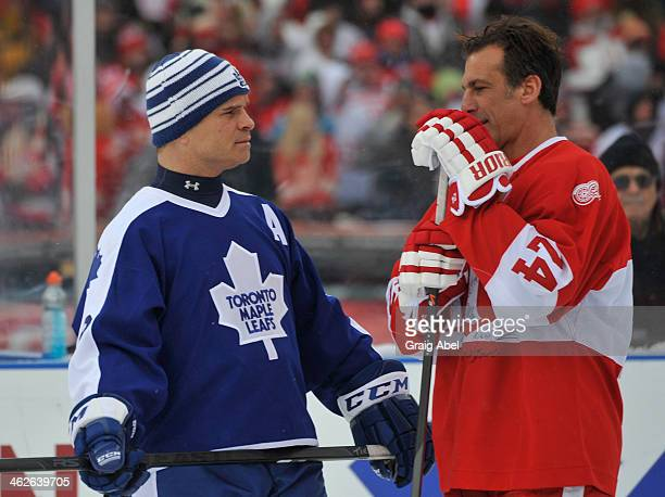Tie Domi of the Toronto Maple Leafs Alumni talks with Chris Chelios of the Detroit Red Wings Alumni have a chat prior to the game on December 31 2013...