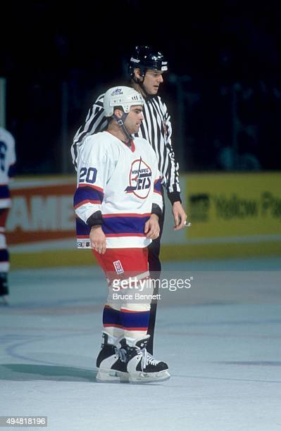 Tie Domi of the Winnipeg Jets is escorted to the penalty box after a fight during an NHL game against the Calgary Flames on January 20 1995 at the...
