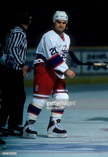Tie Domi of the Winnipeg Jets is escorted to the penalty box after a fight during an NHL game in March 1995 at the Winnipeg Arena in Winnipeg...