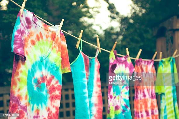 tie dyed tee shirts hanging from a clothes line. - vêtement de peau photos et images de collection