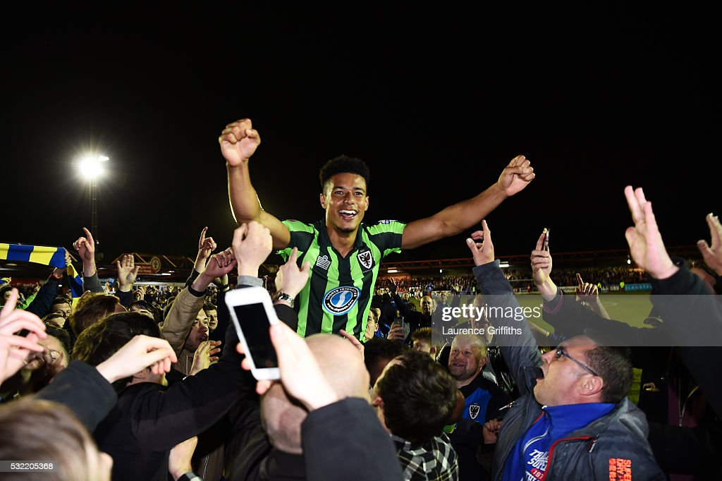 Tie winning goalscorer Lyle Taylor of AFC Wimbledon is carried aloft by the fans after their team wins promotion to League One during the Sky Bet League Two play off, Second Leg match between Accrington Stanley and AFC Wimbledon at The Crown Ground on May 18, 2016 in Accrington, England.