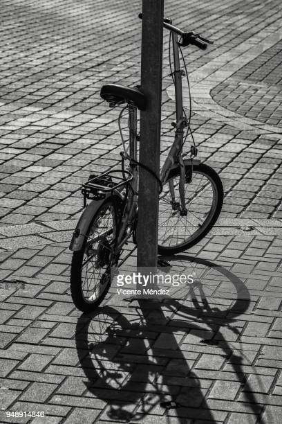 Tied bike and its shadow on the sidewalk