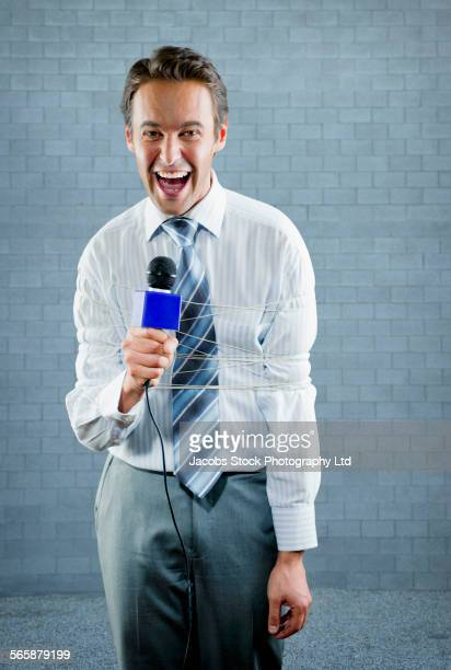 Tied up Hispanic reporter shouting into microphone