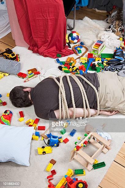 a tied up man in a children's playroom - mann gefesselt stock-fotos und bilder