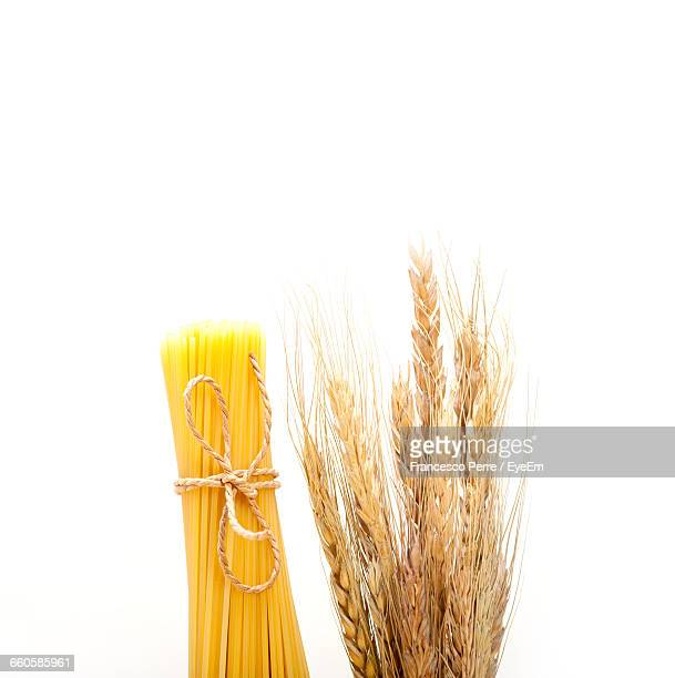 Tied Up Spaghetti And Wheat Over White Background