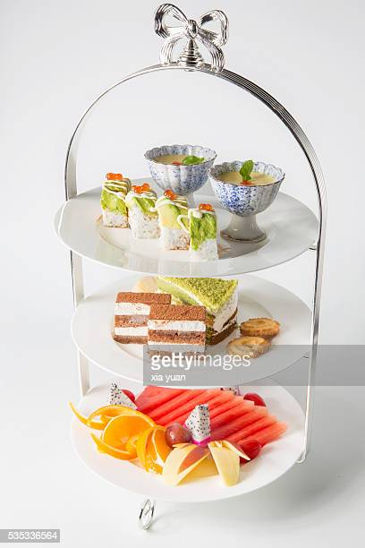 Tiered stand with sushi,pudding,cakes,biscuit and assorted fresh fruits