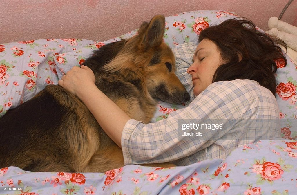 frau schl ft mit hund im bett news photo getty images. Black Bedroom Furniture Sets. Home Design Ideas