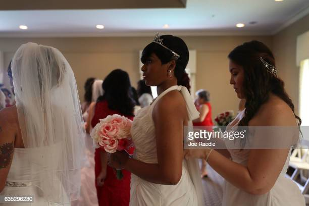 Tierra Hunter gets help with her wedding dress from Madelina de la Cruz as they prepare to participate in a group Valentine's day wedding ceremony at...