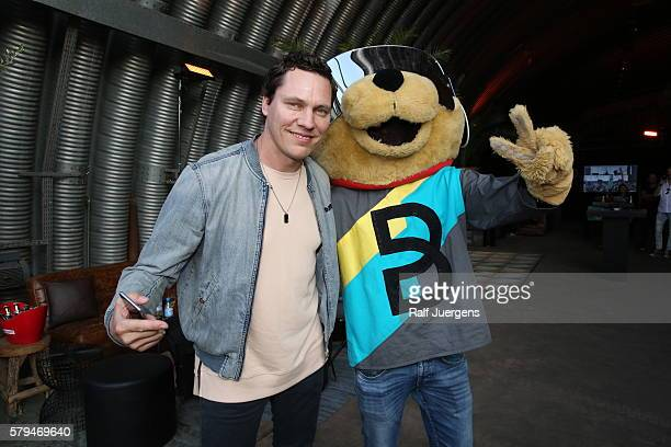 Tiesto and BreuniBaer mascot of Breuninger pose for a photograph at the ParookaVille Festival on July 15 2016 in Weeze Germany