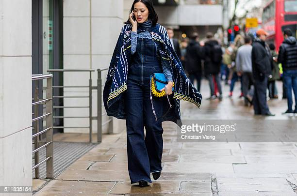 Tifany Hsu is wearing a poncho and a navy denim jumpsuit seen outside Erdem during London Fashion Week Autumn/Winter 2016/17 on February 22 2016 in...