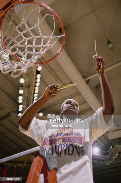 Tiffani Johnson, Center for the Tennessee Lady Volunteers cuts the net on the backboard hoop to celebrate winning the NCAA Division I Women's...