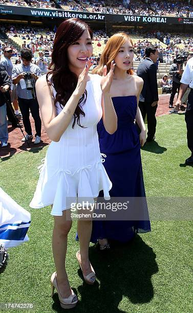 Tiffany and Taeyeon of Korean Pop group Girls Generation take part during Korea Day ceremonies before the game between the Cincinnati Reds and the...