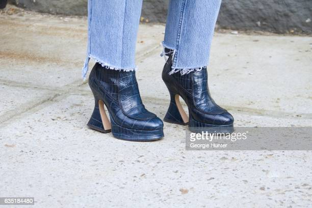 Tiffany Hsu is seen at Spring Studios outside the Phillip Lim show wearing denim jeans with frayed hem and blue snakeskin ankle booties with flared...