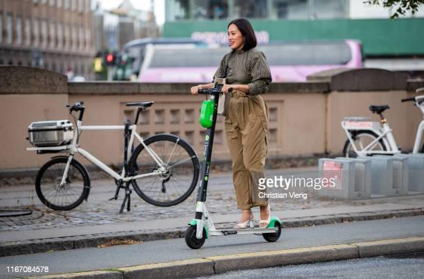 Tiffany Hsu is seen on a Lime e scooter outside Ganni during Copenhagen Fashion Week Spring/Summer 2020 on August 08 2019 in Copenhagen Denmark