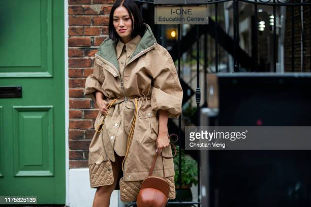 Tiffany Hsu is seen wearing trench coat with belt brown bag outside JW Anderson during London Fashion Week September 2019 on September 16 2019 in...