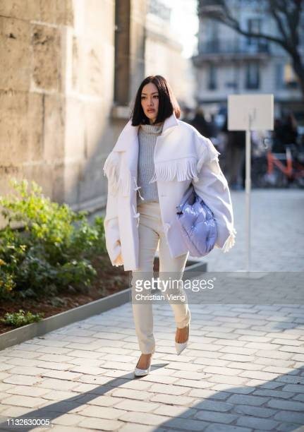 Tiffany Hsu is seen wearing white jacket with fringes Margiela clutch outside Lanvin during Paris Fashion Week Womenswear Fall/Winter 2019/2020 on...