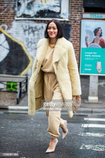 Tiffany Hsu is seen wearing yellow coat, beige pants and jumper, Bottega bag outside Gabriela Hearst during New York Fashion Week Fall / Winter on...