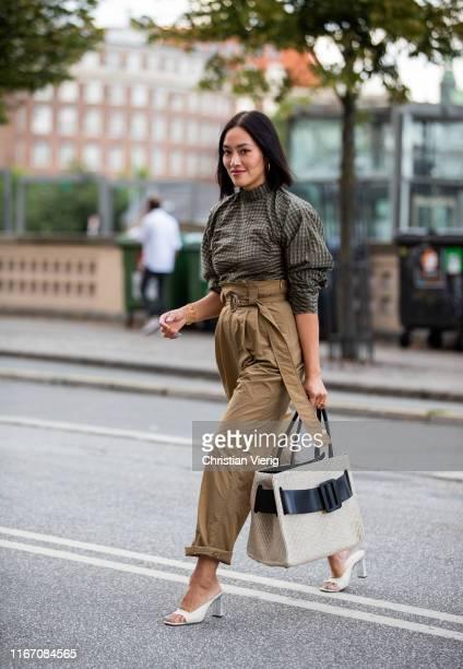 Tiffany Hsu is seenwearing beige high waist pants olive button shirt outside Ganni during Copenhagen Fashion Week Spring/Summer 2020 on August 08...