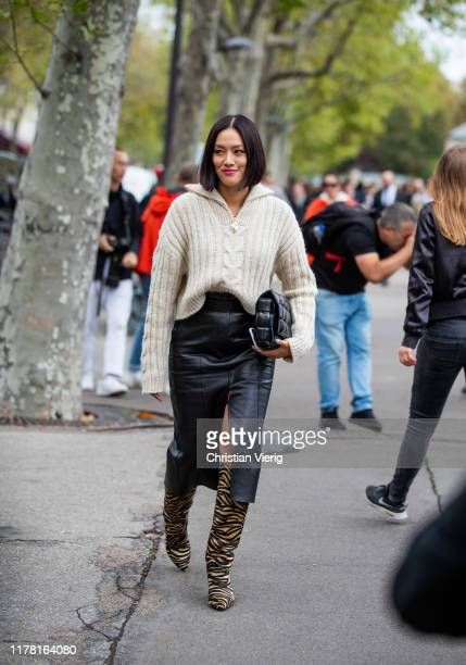 Tiffany Hsu seen wearing black leather skirt with slit knit boots with animal print black bag outside Valentino during Paris Fashion Week Womenswear...