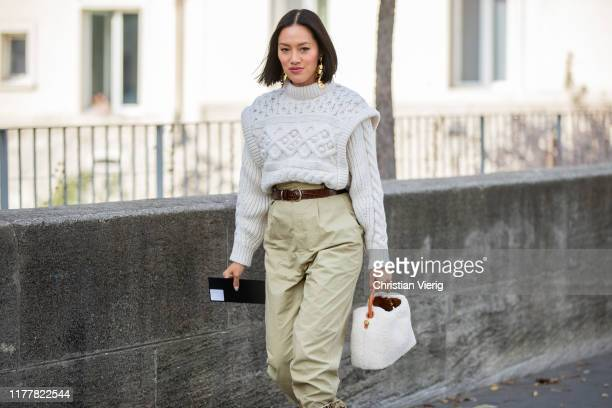 Tiffany Hsu seen wearing cropped knit, beige pants, white bag, boots with snake print outside Haider Ackermann during Paris Fashion Week Womenswear...