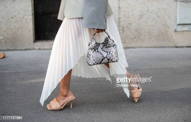 Tiffany Hsu seen wearing white pleated skirt bag with snake print Bottega Veneta heels grey blazer outside Alessandra Rich during Paris Fashion Week...