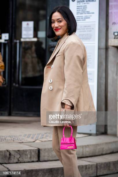 Tiffany Hsu, wearing a beige jumper, beige suit and hot pink mini bag, is seen in the streets of Paris before the Acne Femme show on January 20, 2019...