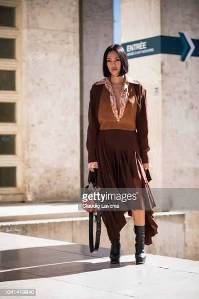 Tiffany Hsu wearing a brown dress black boots and black and red bag is seen after the Marques Almeida show on September 26 2018 in Paris France
