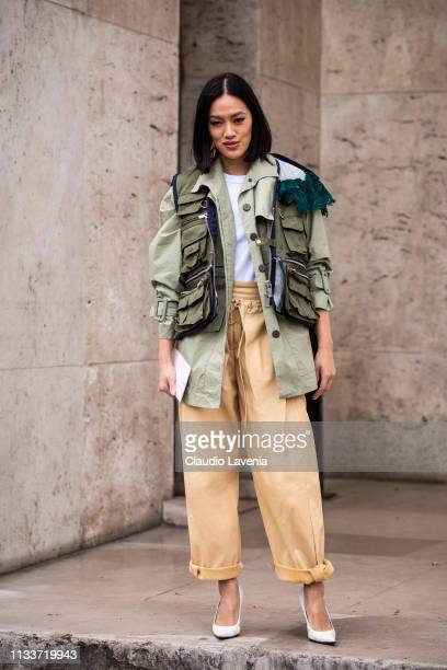 Tiffany Hsu wearing a green decorated jacket beige pants and white heels is seen outside Sacai on Day 8 Paris Fashion Week Autumn/Winter 2019/20 on...