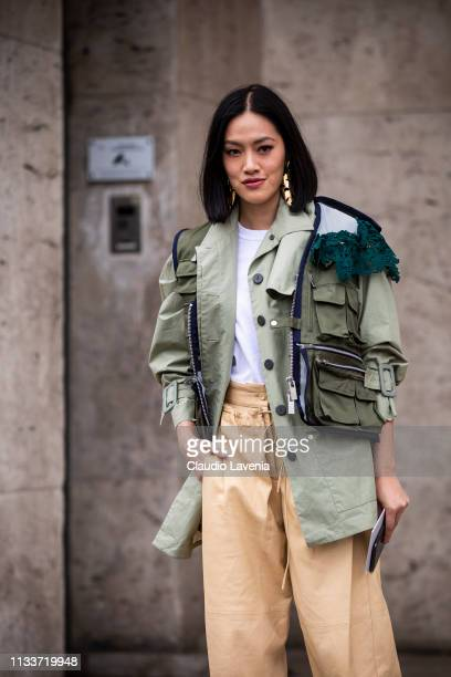 Tiffany Hsu, wearing a green decorated jacket, beige pants and white heels, is seen outside Sacai on Day 8 Paris Fashion Week Autumn/Winter 2019/20...